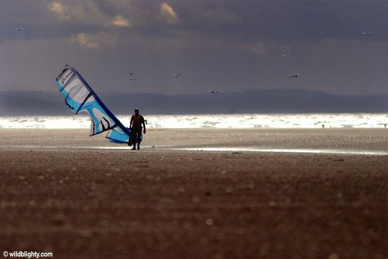 Kitesurfer walking up the beach at Ainsdale at popular Kitesurfing location.
