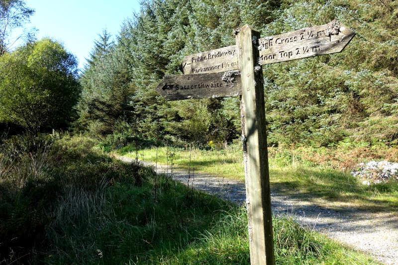 A wooden sign within the forest, to Parkamoor via a bridleway.