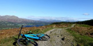 Mountain bike on bridleway with forest and mountains beyond.