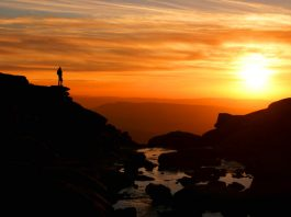 Sunset at Kinder Downfall with walker silhouetted against mountain backdrop